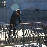 TIMISOARA, ROMANIA -12.13.2016 Happy boy dressed in black climbs a metal fence in a public squuared. royalty free stock photography