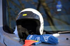 TIMISOARA, ROMANIA- 11. 11.2018 Helmet and gloves belonging to a car race pilot placed on the hood of the car before the race. royalty free stock images