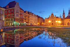 Timisoara, Romania. Night scene in Unirii Square (Union Square), Timisoara, Romania featuring a row a historic houses, reflecting in a temporary pool Stock Photos