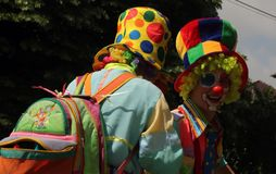 TIMISOARA, ROMANIA- 06.25.2017 Two young people dressed as clowns wearing colorful clothes, curly wigs and big hats laugh cheerful stock photo