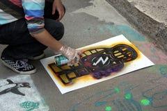 TIMISOARA, ROMANIA 05 30 Un artista di 2009 graffiti disegna la figura facendo uso di uno stampino fotografia stock libera da diritti