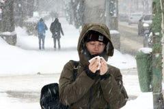TIMISOARA, ROMANIA 02 28 2018 una donna con un cappuccio sulla sua testa pulisce il suo naso durante precipitazioni nevose pesant fotografia stock libera da diritti