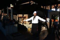 TIMISOARA RUMÄNIEN 11 28 2017 en man med en mustasch som kläs som en kock, bära vita cook's hatt, honnörer med hans breda nolla royaltyfri bild