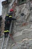 TIMISOARA RUMÄNIEN 03 13 Tar a-brandmannen bort 2011 som oavkortad skyddsutrustning klättrade på en stege, stycken av väggen som  arkivfoton