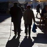 TIMISOARA, RUMÄNIEN -12 13 Weg mit 2016 alter Paaren Hand in Hand auf einer Straße im alten Stadtzentrum in volles Sonnenlicht stockfotografie