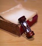 Timmeexponeringsglas och gamla böcker. Arkivfoton
