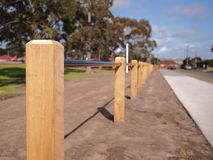 Timmerbarriärpolen och barriärröret mellan en väg och ett offentligt parkerar Royaltyfri Foto
