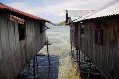 Timmerbyggnader med högar på havskusten Royaltyfria Bilder