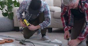 Timmerlieden die een schroevedraaier gebruiken aan schroef in een metaalkader stock video