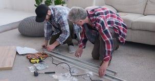 Timmerlieden die schroef op metaalkader thuis aanhalen stock video