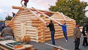 Timmerlieden die vierkante houtdaksparren opheffen aan het dak royalty-vrije stock afbeelding
