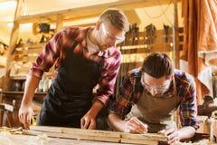 Timmerlieden met heerser en houten plank op workshop royalty-vrije stock afbeeldingen