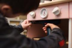 Timmerman aan het werk die de oven van de spelkeuken maken Het bevestigen van deurscharnieren met schroevedraaier royalty-vrije stock foto