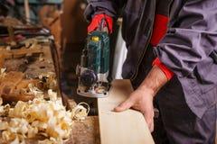 Timmerman aan het werk met elektrische planer schrijnwerkerij stock foto's