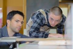 Timmerman With Apprentice Looking bij Plannen in Workshop royalty-vrije stock afbeelding