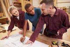 Timmerman With Apprentices Looking bij Plannen in Workshop stock afbeeldingen