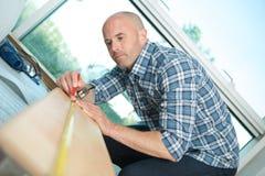 Timmerman die aan hand werken die houten raad met heerser meten stock afbeeldingen