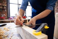 Timmerman die aan houtbewerkingsmachines werken in timmerwerkwinkel Het mensenwerk in een timmerwerk winkelt royalty-vrije stock afbeelding