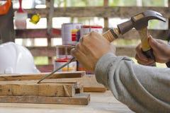Timmerman die beitel en hamer in zijn hand met plank gebruiken Sluit omhoog Stock Foto's
