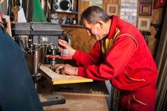 Timmerman die boorpers gebruiken aan maegat in houten plank Stock Afbeeldingen