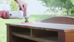 Timmerman die een houten lijst met een elektrische schuurmachine in workshopclose-up oppoetsen stock video