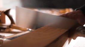 Timmerman die een houten spatie met een Japanse zaag zagen stock videobeelden