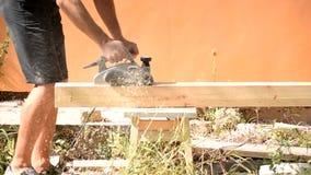 Timmerman die een houten straal met elektrisch houten planer hulpmiddel schaven stock video