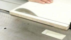Timmerman die met cirkelbladzaag werken, verdelend wit houten bureau stock footage