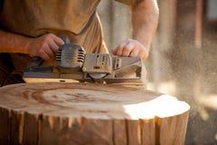 Timmerman die met elektrische planer aan houten stomp in openlucht werken stock afbeelding