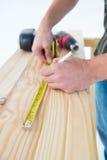 Timmerman die met maatregelenband op plank merken Stock Afbeeldingen