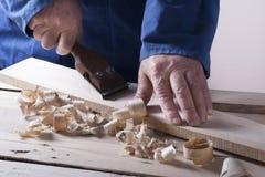 Timmerman die met vliegtuig aan houten achtergrond bij Bouwterrein werken Schrijnwerkerswerkplaats Royalty-vrije Stock Afbeelding