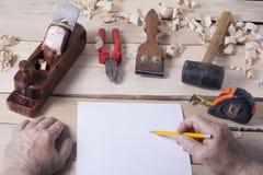 Timmerman die met vliegtuig aan houten achtergrond bij Bouwterrein werken Schrijnwerkerswerkplaats Royalty-vrije Stock Foto's