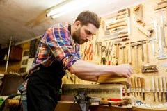 Timmerman die met vliegtuig en hout op workshop werken Royalty-vrije Stock Foto