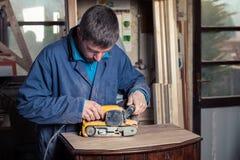 Timmerman die meubilair met riemschuurmachine herstellen royalty-vrije stock afbeeldingen