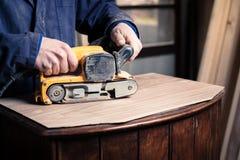 Timmerman die meubilair met riemschuurmachine herstellen stock foto