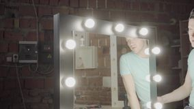 Timmerman die spiegel met lichten controleren als zijn werk of niet werkt Hand productie De Craftmanwerken in een workshop stock videobeelden