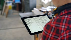 Timmerman die tablet in workshop gebruiken die ontwerp van meubilair op het scherm bekijken stock videobeelden