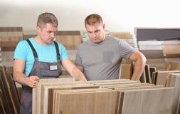 Timmerman die zijn klant helpen om materialen te kiezen stock afbeelding