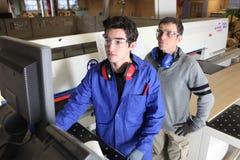 Timmerman en leerling in workshop stock afbeelding