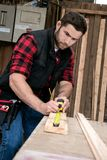 Timmerman, het houten arbeiderswerk die, en houtproduct meten boren maken stock afbeelding