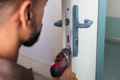 Timmerman Installing Door Lock met Draadloze Schroevedraaier stock afbeelding