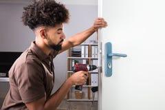Timmerman Installing Door Lock met Draadloze Schroevedraaier stock afbeeldingen