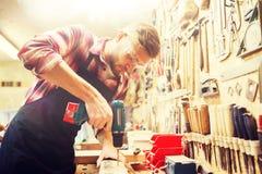 Timmerman met boor boorplank op workshop royalty-vrije stock fotografie