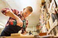 Timmerman met boor boorplank op workshop stock fotografie