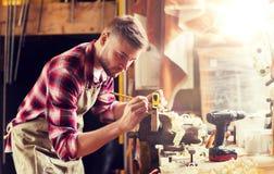 Timmerman met heerser die plank meten op workshop stock foto's