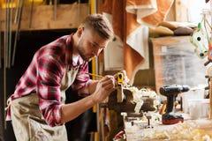Timmerman met heerser die plank meten op workshop royalty-vrije stock afbeeldingen