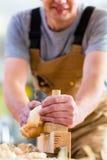 Timmerman met houten planer en werkstuk in timmerwerk stock foto