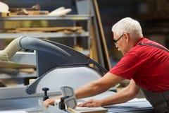 Timmerman met paneelzaag en houtvezelplaat bij fabriek stock foto