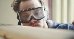 Timmerman In Protective Glasses die Hout onderzoeken stock footage