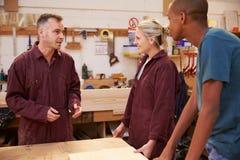 Timmerman Talking To Apprentices in Timmerwerkworkshop stock foto's